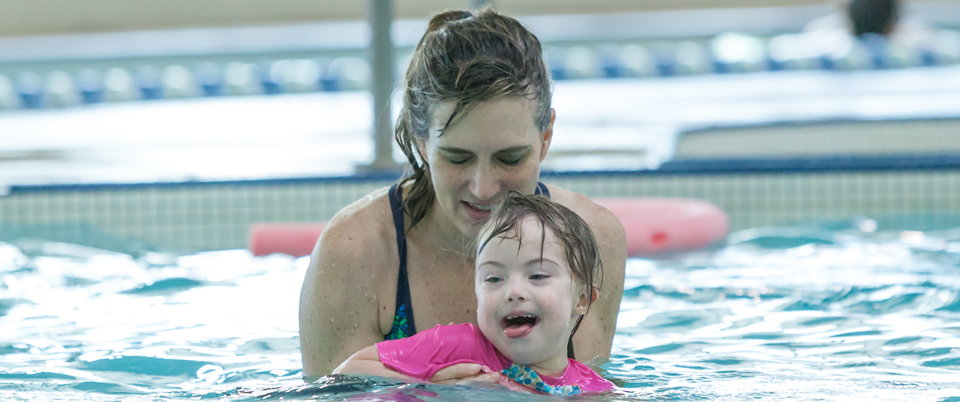 young girl and volunteer in pool